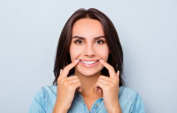 smiling woman pointing at her teeth