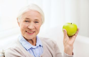 old woman smiling and holding an apple