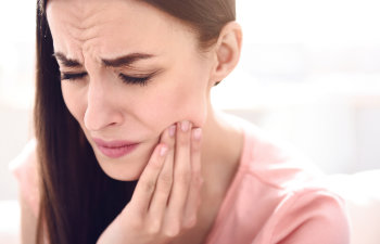 woman touching her mouth because of a toothache