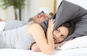 Woman with Pillow Over Her Head Due to Partner's Snoring